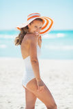 Smiling young woman in hat standing on beach Royalty Free Stock Image