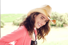 Smiling young woman with hat standing outside Stock Images