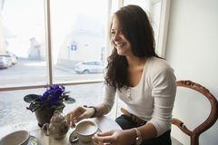 Smiling young woman having coffee at cafe Royalty Free Stock Photos
