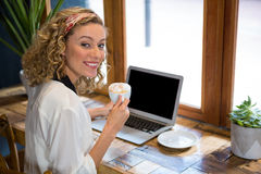 Smiling young woman having coffee while using laptop at cafe. Portrait of smiling young woman having coffee while using laptop at cafe Royalty Free Stock Images
