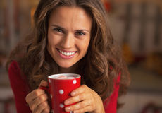 Smiling young woman having cup of hot chocolate with marshmallow Stock Photo