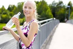 Smiling young woman having her break after working out Royalty Free Stock Photography
