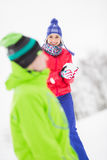 Smiling young woman having snowball fight with male friend Stock Photos