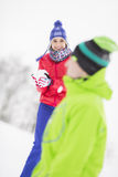 Smiling young woman having snowball fight with male friend Royalty Free Stock Image