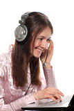 Smiling young woman with headphones and laptop Stock Photo