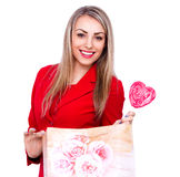 Smiling young woman with heart shaped lollipop and present bag on white Stock Images