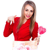 Smiling young woman with heart shaped lollipop and present bag on white Royalty Free Stock Photos