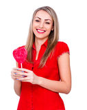 Smiling young woman with heart shaped lollipop on white Royalty Free Stock Images