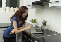 Smiling young woman with her computer in the kitchen Stock Images