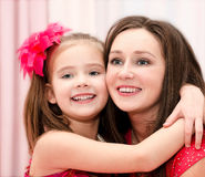 Smiling young woman and her little girl Stock Photos
