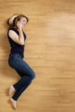 Smiling young woman with her mobile phone on the floor Stock Photo