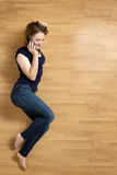 Smiling young woman with her mobile phone on the floor Royalty Free Stock Image