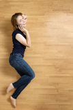Smiling young woman with her mobile phone on the floor Royalty Free Stock Photography