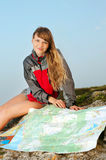 Smiling young woman hiker sitting on the top of mountain Stock Photo