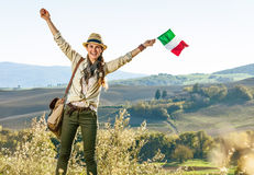 Smiling young woman hiker on Tuscany hike with Italian flag Stock Images