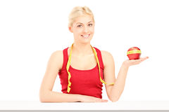 Smiling young woman holding an apple and a measuring tape Stock Photos