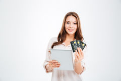 Smiling young woman holding bank card and tablet computer Royalty Free Stock Image