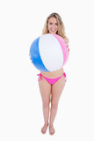 Smiling young woman holding a beach ball Stock Photo