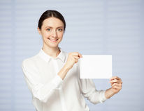 Smiling young woman holding a blank Royalty Free Stock Image