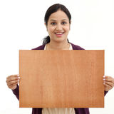 Smiling young Woman holding blank wood sheet Stock Photo