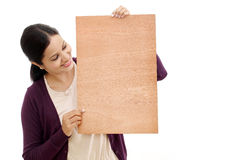 Smiling young Woman holding blank wood sheet Royalty Free Stock Photography