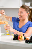 Smiling young woman holding a blender with a fruit smoothie Stock Images