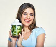 Smiling young woman holding blender with green smoothy ingredien. Ts. Isolated studio portrait Stock Photo