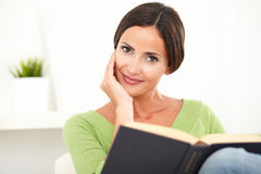 Smiling young woman holding a book. Horizontal portrait of a smiling young woman holding a book with head in hand gesture Royalty Free Stock Photography