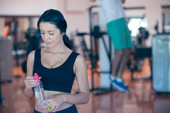 Smiling young woman holding bottle with water in gym. Royalty Free Stock Images