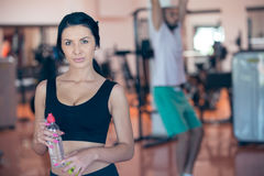 Smiling young woman holding bottle with water in gym. Smiling young women holding bottle with water in gym Stock Image