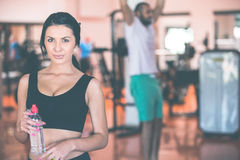 Smiling young woman holding bottle with water in gym. Smiling young women holding bottle with water in gym Royalty Free Stock Photos