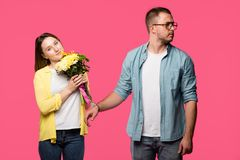 smiling young woman holding bouquet of flowers while standing in handcuffs with man looking away isolated