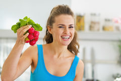 Smiling young woman holding bunch of radishes Stock Image