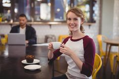 Smiling young woman holding coffee cup while sitting at cafe. Portrait of smiling young women holding coffee cup while sitting at table in cafe Stock Photo