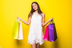 Smiling young woman holding colorful shopping bags  on yellow. Royalty Free Stock Images