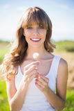 Smiling young woman holding dandelion Stock Photography