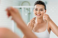 Smiling young woman holding dental floss and looking at mirror. In bathroom stock image