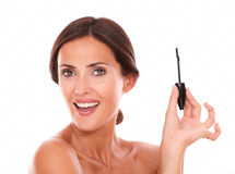 Smiling young woman holding eyelash brush royalty free stock photo