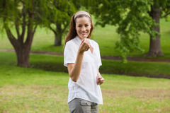 Smiling young woman holding a flower at park Stock Photography
