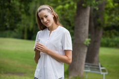 Smiling young woman holding a flower at park Royalty Free Stock Photography
