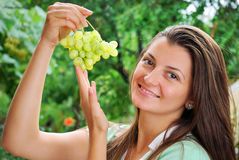 Smiling young woman holding fresh grapes in the garden Royalty Free Stock Images