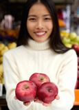 Smiling young woman holding fresh organic red apples in hand Royalty Free Stock Photo