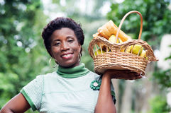 Smiling young woman holding a fruit basket. Stock Image