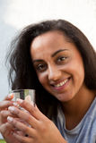 Smiling Young Woman Holding a Glass of Water. Close up Smiling Pretty Young Woman Holding a Glass of Water with her Both Hands while Looking at the Camera Stock Photo