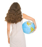 Smiling young woman holding globe. Rear view Stock Image