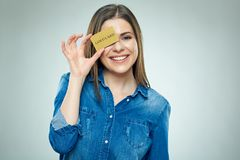 Smiling young woman holding gold credit card against her eye. Stock Image