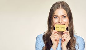 Smiling young woman holding gold credit card. Isolated portrait Stock Photo