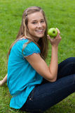 Smiling young woman holding a green apple Royalty Free Stock Photos