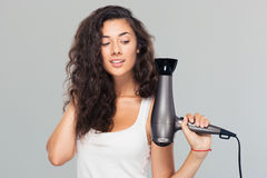 Smiling young woman holding hairdryer Royalty Free Stock Photo