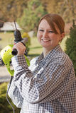 Smiling young woman is holding a hand drill. Stock Photos